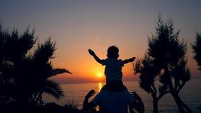 Pysen sitter på mannens skuldror och ser solnedgång Fader och son arkivfilmer