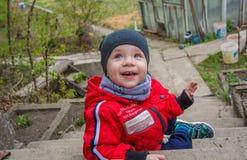 Pysen sitter på momenten av trappuppgången, ler spelar behandla som ett barn och på a fotografering för bildbyråer