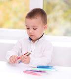 Pysen skriver genom att använda en penna Royaltyfri Foto