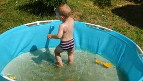 Pysen som åldras ett år, badas i konstgjort behandla som ett barn pölen på varm sommardag lager videofilmer
