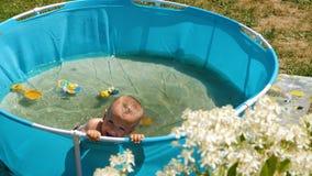 Pysen som åldras ett år, badas i konstgjort behandla som ett barn pölen på varm sommardag stock video