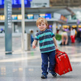 Pysen som går på semestrar, snubblar med resväskan på flygplatsen Royaltyfri Bild
