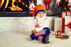 Pysen som kläs som julälva, sitter och är ledsen under trädet och väntar på jultomten arkivfoton
