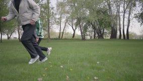 Pysen som spelar fotboll, eller fotboll med hans fader eller farfar i parkerar Barnet som f?rs?ker att v?lja upp bollen arkivfilmer