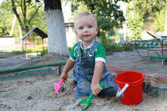 Pysen som spelar i sandlådan Royaltyfria Foton