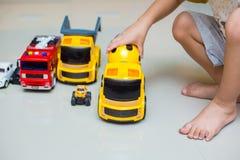 Pysen spelar leksakbilar hemma royaltyfri fotografi