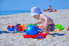 Pysen spelar leksaker i sand på stranden arkivfoton