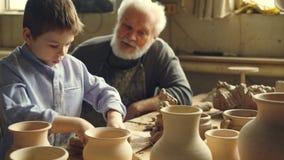 Pysen spelar med lerasammanträde med hans morförälder på tabellen i hem- krukmakeristudio Farfadern talar till lager videofilmer