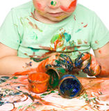 Pysen spelar med målarfärger Arkivfoto