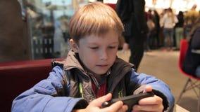 Pysen spelar med telefonen i kafé Blond pojke med en telefon arkivfilmer