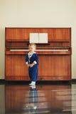 Pysen spelar pianot Arkivbild