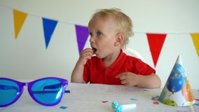 Pysen suger en söt godis på en pinne Efter födelsedagparti Gimbalskott arkivfilmer