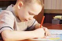 Pysen tecknar med blyertspennor i en förskriftsbok arkivbilder