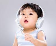 Pysen tycker om lyssnar till musik Arkivbild