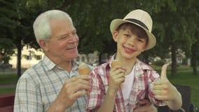 Pysen visar upp hans tumme nära hans morfar royaltyfria foton