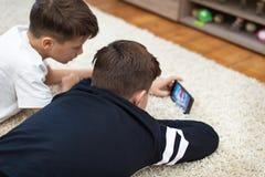 Pyser som håller ögonen på videoen vid smartphonen på matta arkivfoton