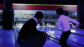 Pysförsök att spela en lek av bowlingen med fadern arkivfilmer