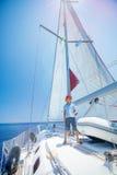 Pyskapten ombord av seglingyachten på sommarkryssning Resa affärsföretaget som seglar med barnet på familjsemester Arkivfoton