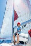 Pyskapten ombord av seglingyachten på sommarkryssning Resa affärsföretaget som seglar med barnet på familjsemester Royaltyfri Foto