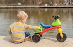 Pyssammanträde och lek med hans rinnande cykel arkivfoto