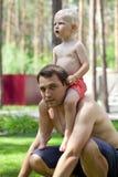 Pyssammanträde på skuldrorna av en ung fader royaltyfri fotografi