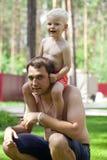 Pyssammanträde på skuldrorna av en ung fader arkivbild