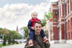 Pyssammanträde på skuldrorna av en ung fader royaltyfri foto