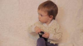 Pyssammanträde på soffan och spela på en smartphone arkivfilmer