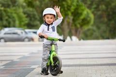 Pysunge i hjälmritt som en cykel i stad parkerar Utomhus- gladlynt barn royaltyfria bilder