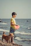 Pysungebarn med hunden som har gyckel på stranden Royaltyfri Fotografi