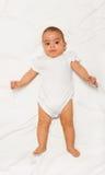 Pyzaty Afrykański mały dziecko jest ubranym białego babygro zdjęcie royalty free