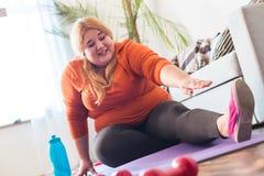 Pyzaty kobieta sport siedzi na matowych rozciąganie nogach koncentrować w domu fotografia stock