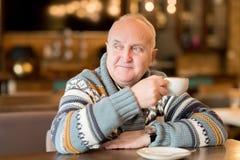 Pyzaty mężczyzna w puloweru obsiadaniu w kawiarni obrazy stock