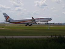 PZ-TCP Surinam Airways Airbus A340 landing on the Buitenveldertbaan 09-27 landing strip at Amsterdam Schiphol Airport in the Nethe. Rlands royalty free stock images