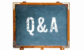 "Q&A,在一个蓝色老脏的葡萄酒木黑板或黑板立场写的""Questions和Answers†白色文本的首字母缩略词 库存照片"