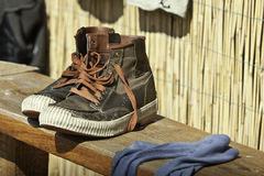 Old shoes on a wooden board. Q pair of old shoes on a wooden board in Vadu Royalty Free Stock Photo