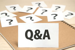 Q&A or Questions and Answers on a piece of paper and many question marks on notebook. stock images