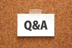 Q&A or Questions and Answers on a piece of white paper on a brown cork board. Q&A or Questions and Answers concept. Stock Photo