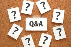 Q&A or Questions and Answers on a piece of white paper and many question marks on brown cork board. Q stock image
