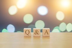 QA questions answers on 3 wooden cubes on a beautiful bokeh blurred background. With lights Royalty Free Stock Photo