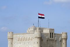 Qaitbay Fortress - Alexandria Egypt. Qaitbay citadel is located on the coast of Alexandria (the second largest city in Egypt). Egyptian flag hovering over the Royalty Free Stock Photos