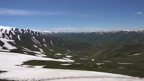 Qalai Khumb to Dushanbe Khoburobot Pass. Breathtaking Panoramic View with Snow Capped Mountains and Green Grass Valley at Background on a Sunny Blue Sky Day stock footage