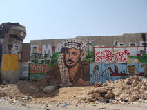 Qalandia wall. Part of the wall separating israel/westbank with the late abu ammar drawing on it royalty free stock images