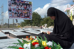 Qana Massacre. Lebanese women is praying near the grave of her family who died in Israel bombardment in Qana, Lebanon Royalty Free Stock Image