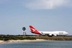 Qantas Boeing 747 with airport tower Royalty Free Stock Photo
