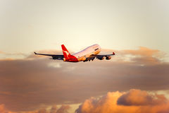 Qantas Boeing 747 jet in flight. Qantas Boeing 747 in flight in late afternoon warm light Royalty Free Stock Photo
