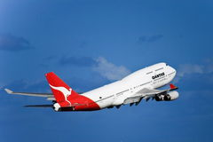 Qantas Boeing 747 jet in flight on a blue sky Stock Images