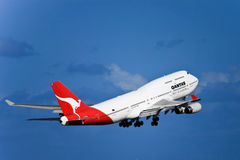 Qantas Boeing 747 jet in flight with landing gear. Royalty Free Stock Image