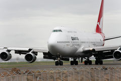 Qantas Boeing 747 jet taxis on the runway. Royalty Free Stock Photo