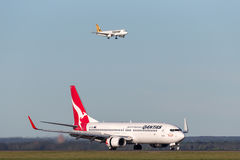 Qantas Boeing 737-800 aircraft at Sydney Airport with a Tiger Airways Airbus A320 on approach in the background. royalty free stock photo
